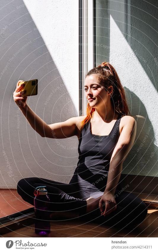 Fitness Frau sitzend und mit Mobiltelefon Raum Training passen Stock Smartphone Wohnzimmer sich[Akk] entspannen Handy Fitnessstudio entspannend Athlet Wellness