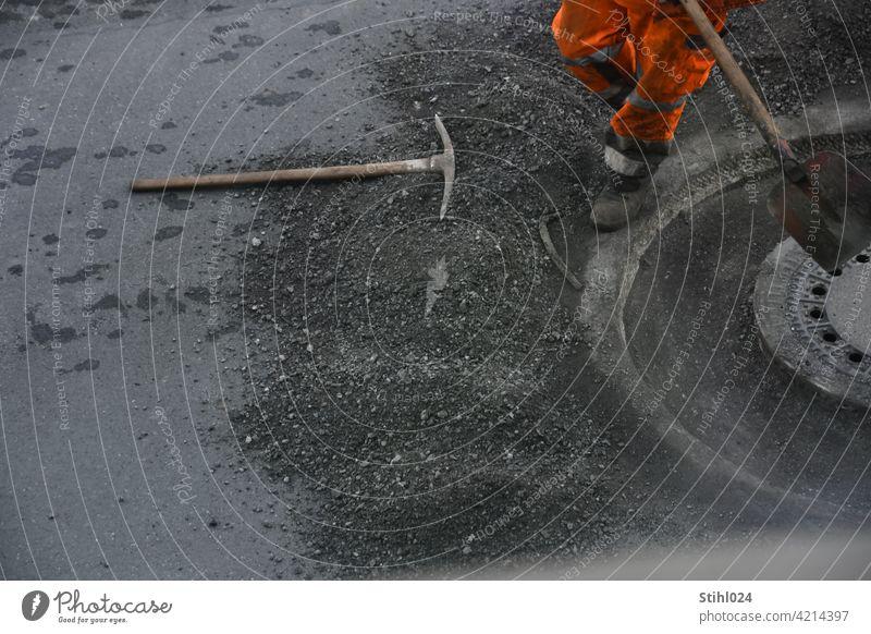 Straßenbauarbeiter mit orangener Hose und Schaufel strassenarbeiter schaufel hose reflektierend arbeiten stemmarbeiten kanaldeckel manhole asphaltarbeiten