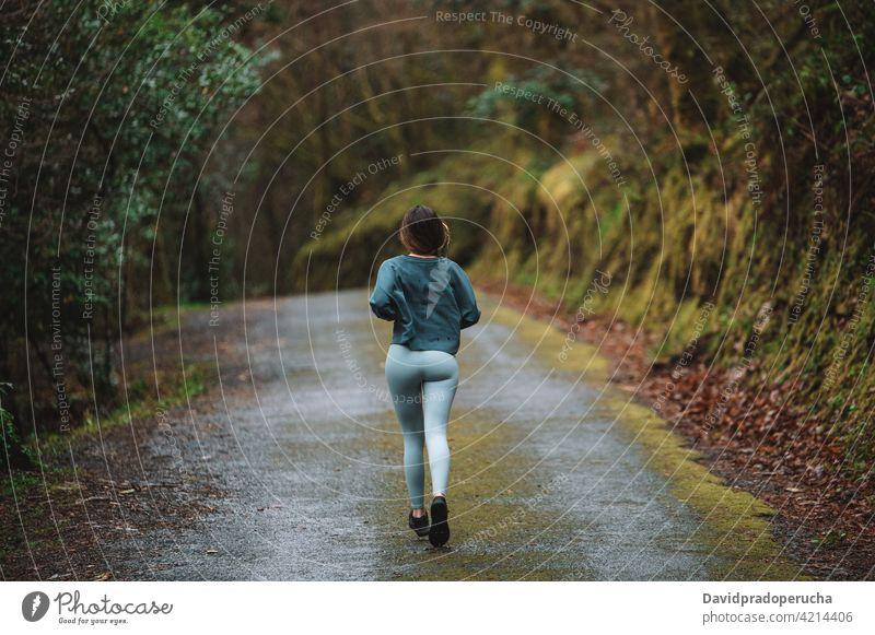 Frau läuft entlang der Straße im Wald laufen Sportlerin Training Läufer Herz sich[Akk] bewegen aktiv Energie Wälder Sportbekleidung Athlet Aktivität Gesundheit