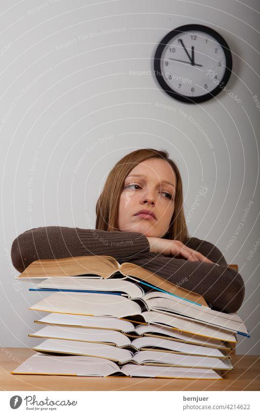 Studentin mit Büchern und Uhr Buch Mädchen Bildung Stress Alarm Schreibtisch Prüfung müde Arbeit Teenager Tisch weiblich Schule Müdigkeit Kaukasisch jung Frau