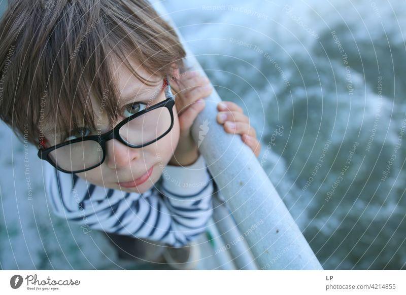 Kind mit Brille, das ein nach oben schauendes Gesicht macht zögernd verwirrt ratlos skeptisch Zweifel zweifelhaft hestitate Unsicherheit Verwirrung Kindheit