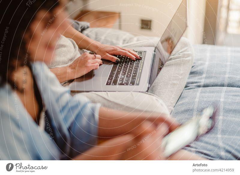 Nahaufnahme der weiblichen Hände tippen auf Laptop-Tastatur zu Hause in der Nähe seiner unerkennbaren Freundin. Business, Arbeit von zu Hause, Studium Online-Konzept.