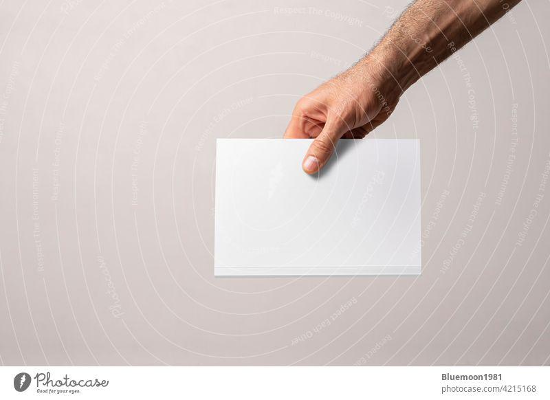 Männliche Hand hält ein geschlossenes Buch-Katalog mit leeren Abdeckung mock-up Attrappe editierbar Wandel & Veränderung katalogisieren Deckung blanko Marke