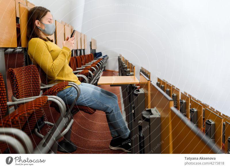 Frau in Gesichtsmaske mit Smartphone Telefon Mitteilung Erwachsener benutzend Bildung Klassenraum Technik & Technologie Mobile Internet Nachricht Anschluss
