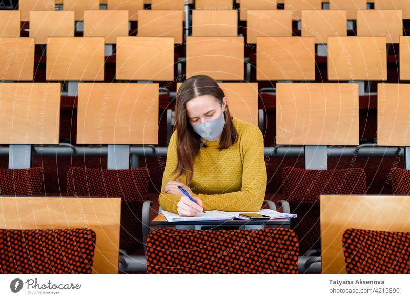 Studentin sitzend mit Gesichtsmaske Bildung Schüler Klassenraum studierend zurück zur Schule Gymnasium Lernen Sicherheit Frau Person im Innenbereich Schutz
