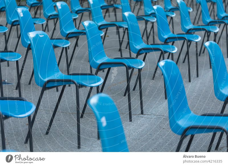 Reihen und Säulen von unscheinbaren blauen Plastikstühlen, aufeinanderfolgend, in einer Linie angeordnet, in ähnlichen Abständen des Raumes, mit Blick auf den gleichen Ort. Retiro Park, Madrid, Spanien.