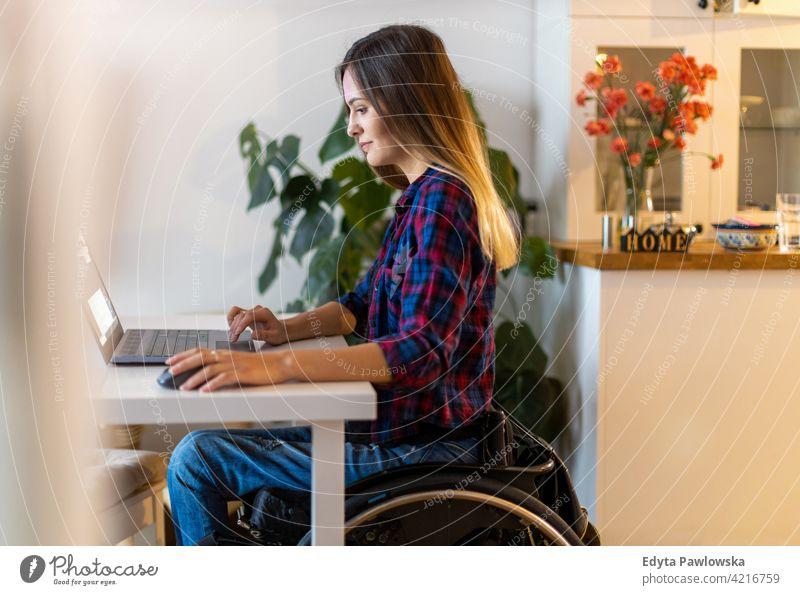 Frau im Rollstuhl benutzt Laptop zu Hause häusliches Leben Behinderung deaktiviert Selbstvertrauen unabhängig im Innenbereich heimwärts Menschen jung