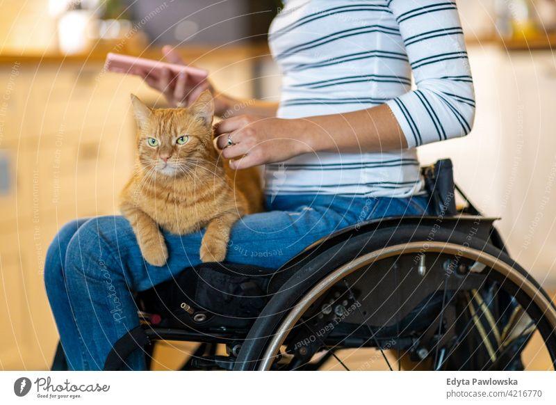 Frau im Rollstuhl mit Katze auf dem Schoß häusliches Leben Behinderung deaktiviert Selbstvertrauen unabhängig im Innenbereich heimwärts Haus Menschen jung