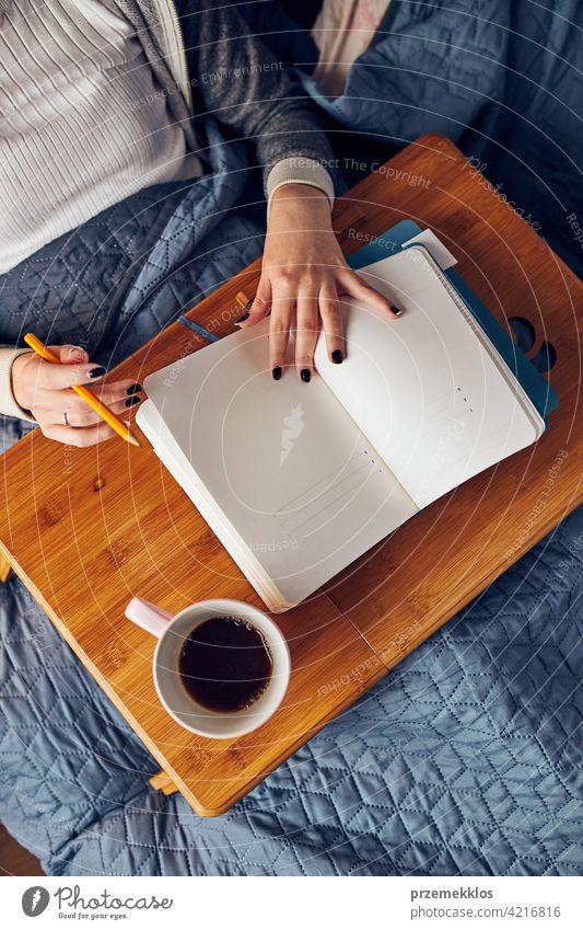 Schüler lernen zu Hause. Junge Frau macht Notizen, Lesen und Lernen von Notizblock. Mädchen schreiben Journal sitzen im Bett Bildung im Innenbereich arbeiten