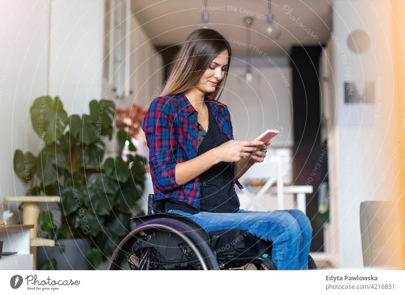 Frau im Rollstuhl auf Smartphone zu Hause häusliches Leben Behinderung deaktiviert Selbstvertrauen unabhängig im Innenbereich heimwärts Menschen jung
