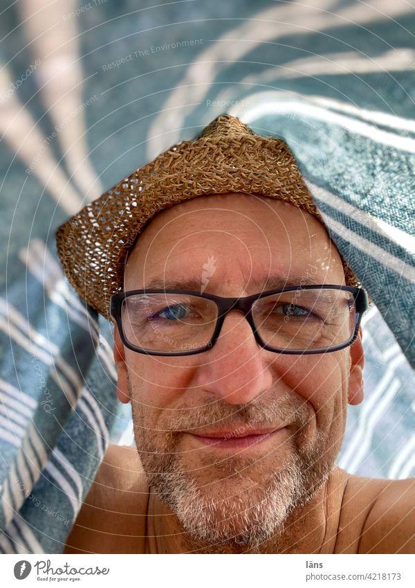Strandleben unterm Strandtuch Mann Porträt Zufriedenheit Erwachsene Blick Strohhut Dreitagebart Brille Brillenträger Mensch 1 Blick in die Kamera Kopf selfie
