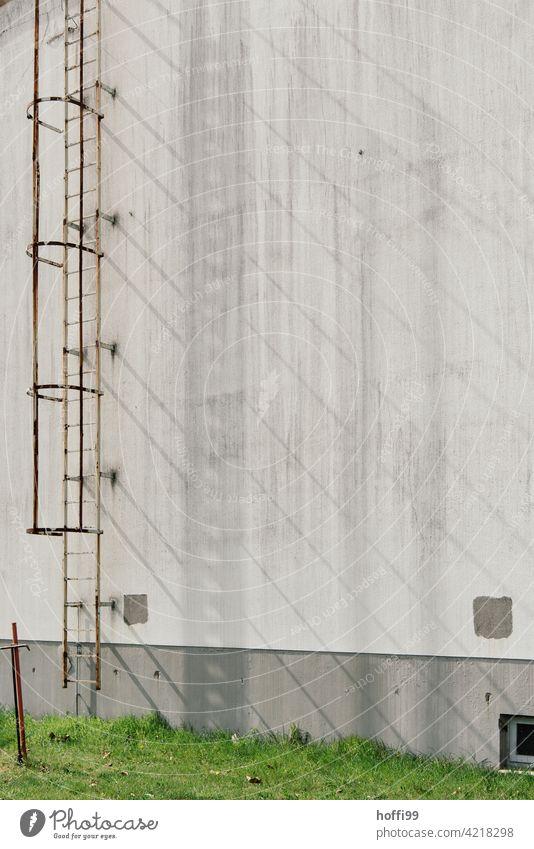Schattenwurf einer Aussenleiter auf grauer Wand rostig fluchtleiter Leiter Fluchtweg Lagerhalle Hafen Fassade Industrie Industriefotografie Lagerhaus