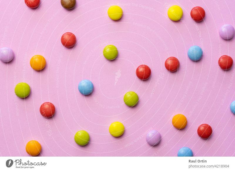Bunte Schokolade Bonbons smarties background.top view Süßigkeiten mehrfarbige Lebensmittel Textur, auf rosa Hintergrund. farbenfroh Smarties Konditorei Bälle