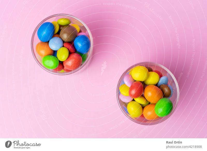 Mehrfarbige Schokolade Bonbons im Glas Glas auf blauem Vintage-Holz background.Top Ansicht bunte Süßigkeiten Hintergrund Konzept mit Kopie Raum für Text.