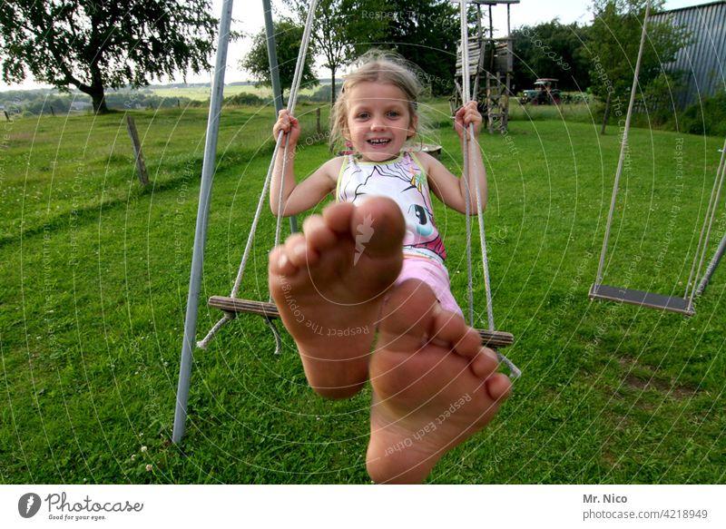 Mädchen schaukelt barfuß im Garten schaukeln Kleinkind Kindheit Spielen Schaukel Spielplatz Bewegung Lebensfreude spass lächeln lachen Schwung Sommer Glück Spaß
