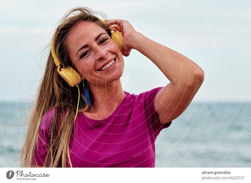 Junge Frau am Strand hört Musik mit gelben Kopfhörern Sommer schön Meer Natur Mädchen jung MEER Hut Erholung Lifestyle im Freien eine Menschen Himmel hören