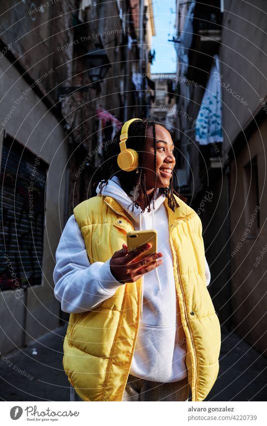 Frau hört Musik mit Kopfhörer und Telefon. che Mobile urban Gerät genießend Technik & Technologie im Freien Afrikanisch Amerikaner Drahtlos hören Smartphone