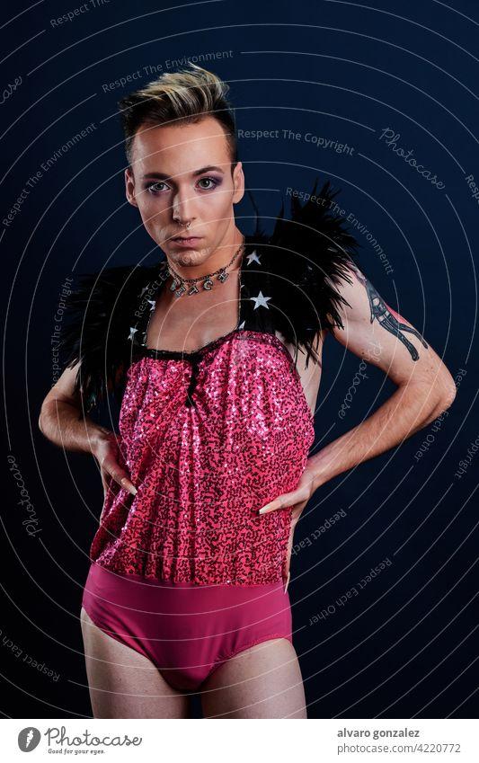 Junge Transgender-Modell mit rosa Kleid und dunkelblauem Hintergrund che Homosexualität Vielfalt feminin Porträt jung Typ Schminke männlich Person Kaukasier