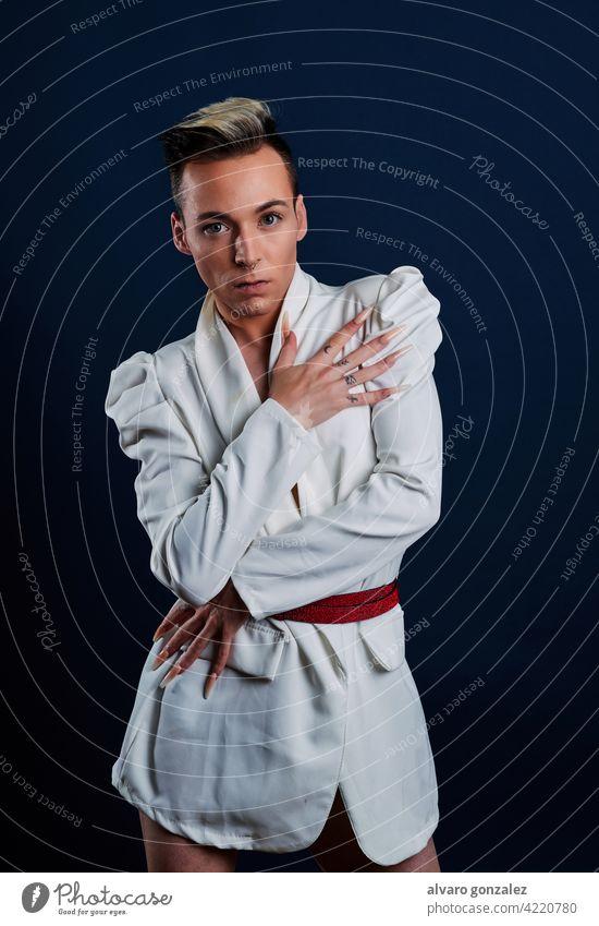 ein Transgender-Modell mit langen Nägeln und einem dunkelblauen Hintergrund che Porträt jung Typ Schminke männlich Person Kaukasier vereinzelt weiß Make-up