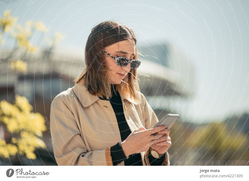 Porträt einer jungen Geschäftsfrau mit ihrem Smartphone in lyon, frankreich. Person Frau Business Kaukasier europa Lifestyle im Freien Unternehmer Cyberspace