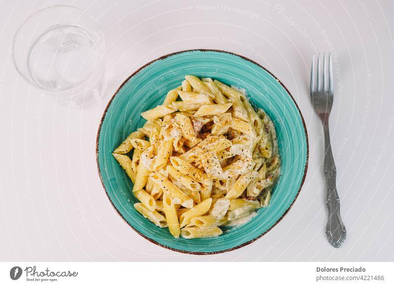 Teller mit Makkaroni mit Sahnesauce, Zwiebel und Leinsamen. Spaghetti appetitlich Bestandteil Italienische Küche Speiseteller schmackhaftes Essen Ernährung