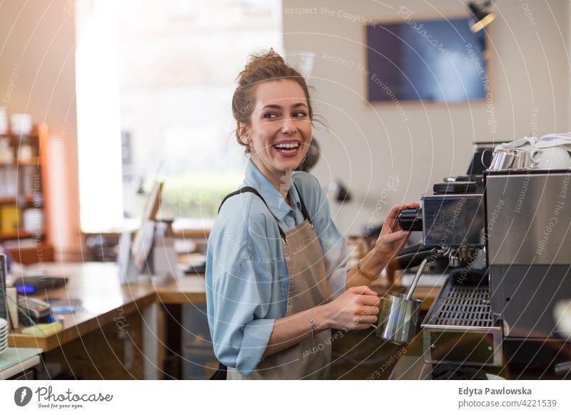 Weibliche Barista macht Kaffee Menschen Frau junger Erwachsener lässig attraktiv Lächeln Glück im Innenbereich Kaukasier zahnfarben genießend Café Restaurant