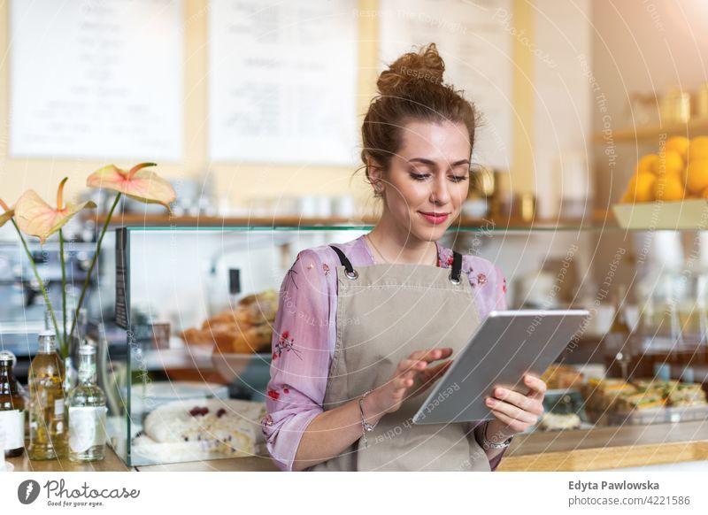 Junge Frau arbeitet in einem Café Menschen junger Erwachsener lässig attraktiv Lächeln Glück im Innenbereich Kaukasier zahnfarben genießend Restaurant Schürze