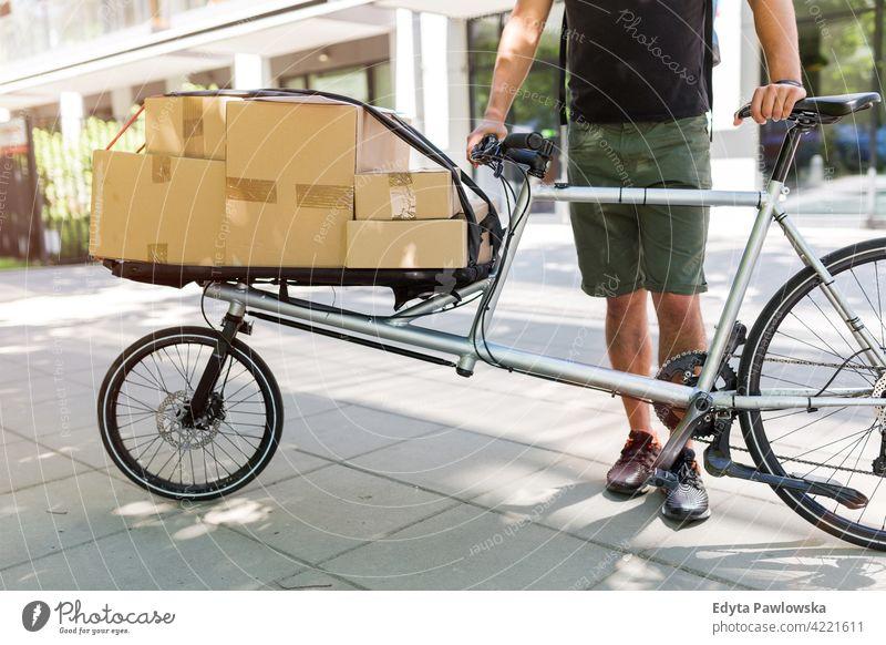 Fahrradkurier bei einer Lieferung Menschen junger Erwachsener Mann männlich Lächeln Glück blauer Kragen Kurier Meldereiter Auslieferer Versand liefernd Paket