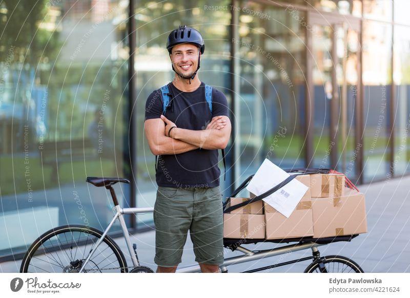 Fahrradkurier, der eine Lieferung auf einem Lastenfahrrad macht Menschen junger Erwachsener Mann männlich Lächeln Glück blauer Kragen Kurier Meldereiter