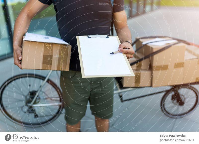 Kurier mit Klemmbrett und Kartons Menschen junger Erwachsener Mann männlich Lächeln Glück blauer Kragen Meldereiter Auslieferer Versand liefernd Paket Pakete