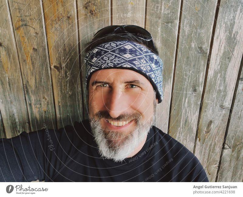 Porträt eines bärtigen Mannes mit hölzernem Hintergrund Bartiger Mann 40-50 Jahre Erwachsene Mensch attraktiv gutaussehend 18-30 Jahre Farbfoto Lifestyle Mode