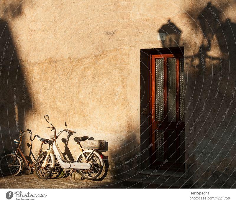 Rad und Mofa an Hauswand in der Morgensonne in Italien Fahrrad moped Schattenspiel Außenaufnahme Motorrad Gebäude parken Haustür Laternenschatten Italienisch