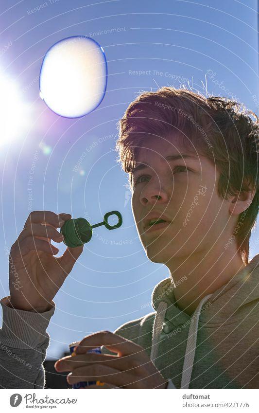 Teenager Junge bläst Seifenblase bei Kälte blasen Freude Spielen Kindheit Farbfoto Himmel fliegen Glück träumen Schweben Blase Außenaufnahme Freiheit Kugel