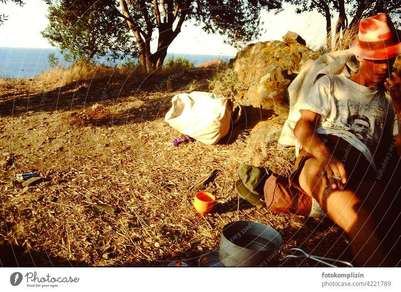cooler junger Mann, der in der Natur auf dem Boden sitzt und raucht Globetrotter Reisende einfaches Leben reisend Auszeit entspannt Ausflug Wohnmobil