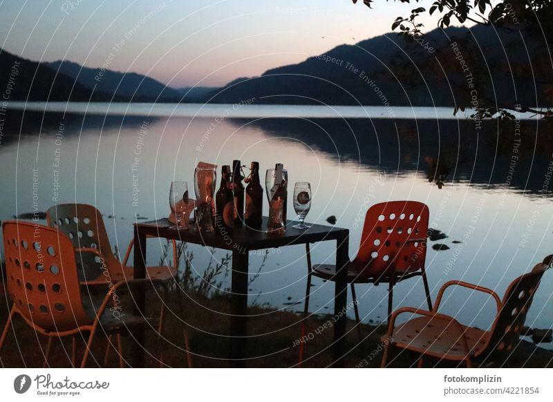 Feierabend oder verlassener Tisch mit Bierflaschen und Stühlen an einem See in der Abenddämmerung Feierabendbier retro Kontakte Beisammensein leer Gastronomie