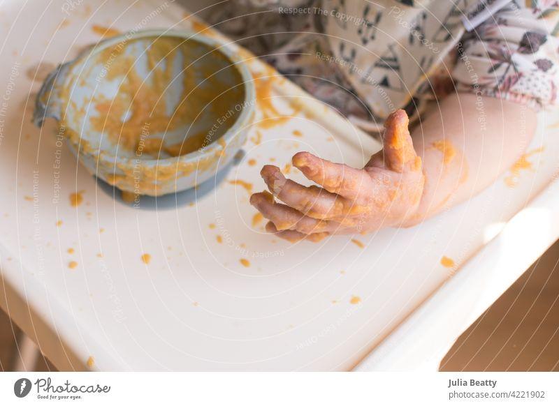 Selbstfütterung: Junges Baby, das ein Durcheinander macht und Püree mit den Händen isst, nach der buchtgeführten Entwöhnung babygeführte Entwöhnung unordentlich