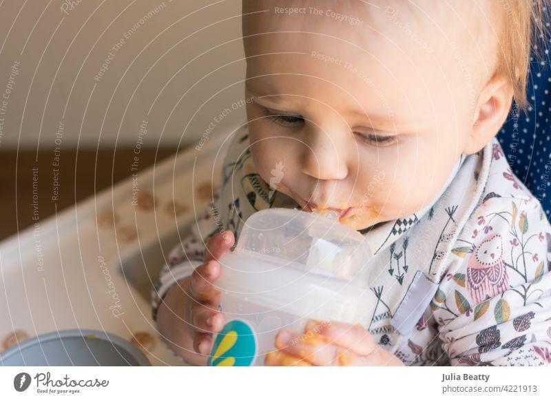 Kleinkind, das lernt, einen Strohhalmbecher zu benutzen, um Wasser zu trinken; Förderung des Lippenschlusses, Anziehen der Wangen und Anheben der Zunge