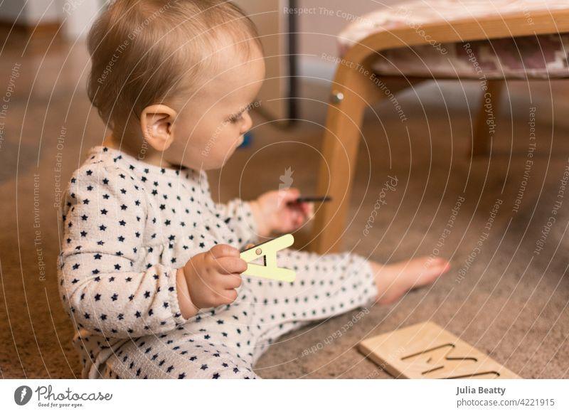 Zehn Monate altes Kleinkind spielt mit einem hölzernen Buchstabenpuzzle auf dem Boden Geduldsspiel Kind Feinmotor Fähigkeiten Zange 10 Monate alt Baby jung