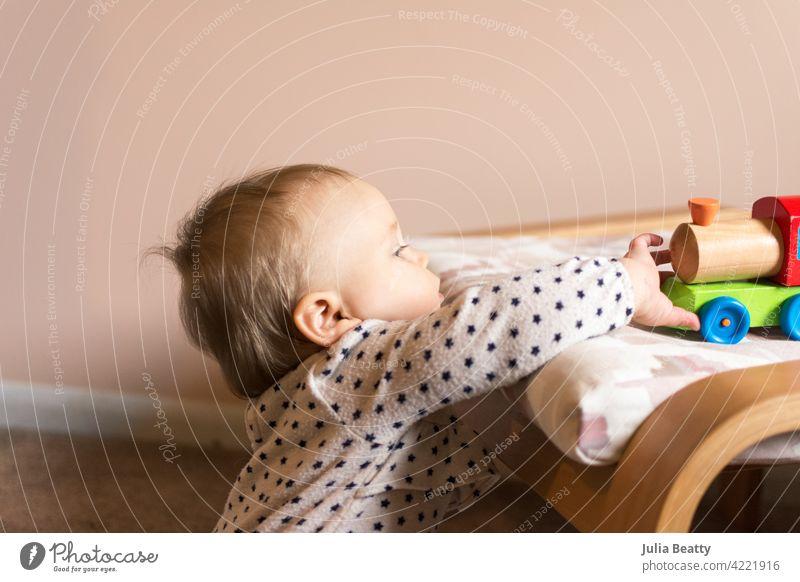 Kleinkind Mädchen erreichen bis zu einem bunten Holzeisenbahn Spielzeug greifen; Pfirsich und weißen Kinderzimmer Feinmotor Fähigkeiten ziehen 10 Monate alt