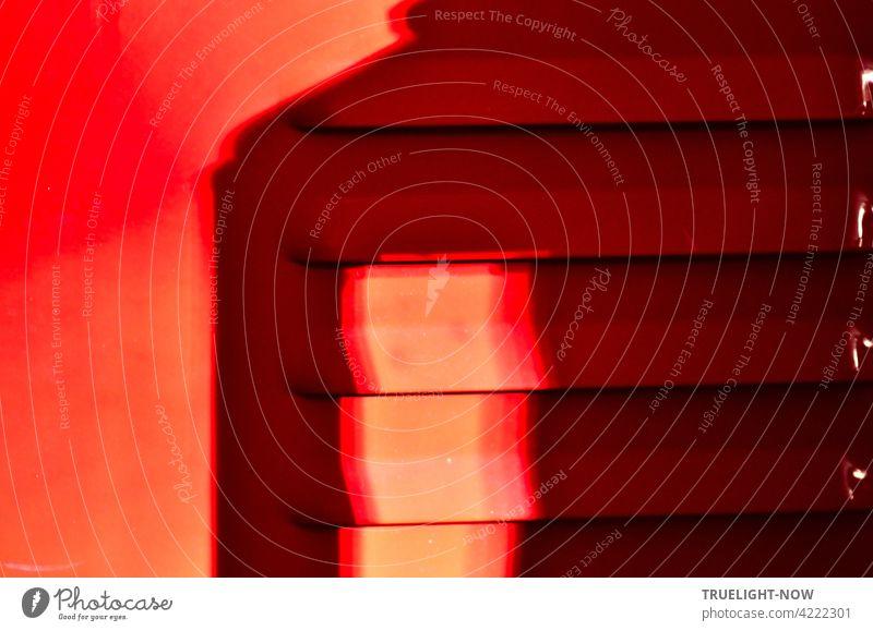 Rot! Sonnenlicht und Schatten auf der Tür (Detail) eines Feuer roten Metallschranks mit Lüftungsschlitzen die an der Seite noch kleine weisse Lichtreflexe zeigen