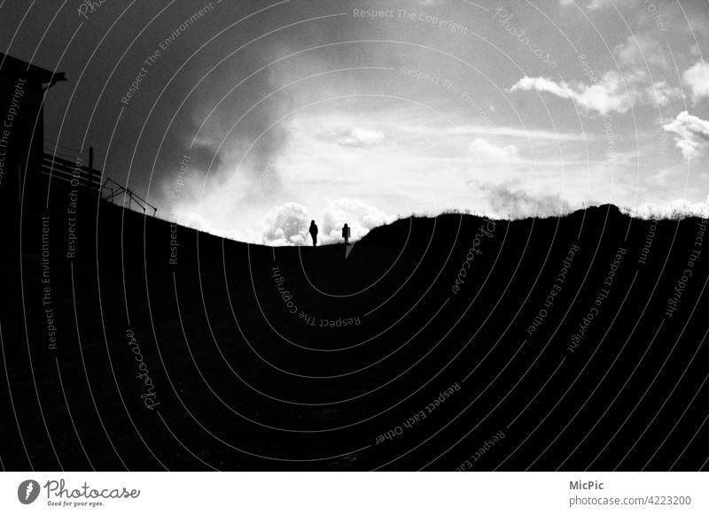 Unwetter zieht auf - zwei Menschen in den Bergen schatten dunkel bedrohlich Wolken Himmel Sturm Gewitter Wetterwechsel Gewitterwolken Natur Außenaufnahme Regen