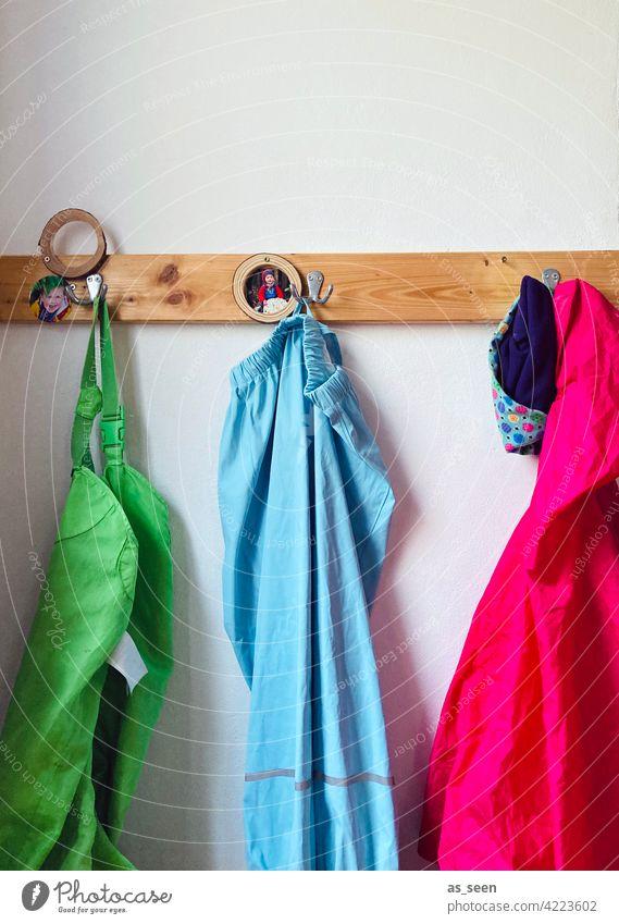 Kindergartengarderobe Garderobe Kindheit Haken aufhängen Kleidung magenta pink hellblau grün Regenhose Regenjacke Garderobenleiste Kleiderhaken Bekleidung