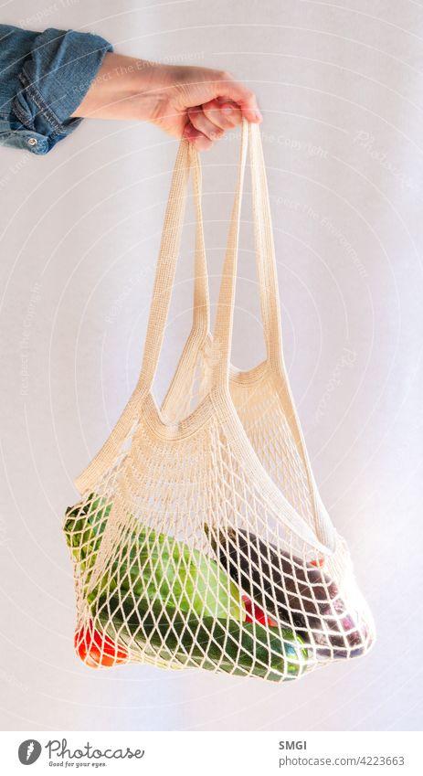 Die Hand einer Frau hält einen Stoffbeutel voller Obst und Gemüse. Plastikfrei. Müllfrei Tasche Bambus Biografie abbaubar kaufen farbenfroh Konzept Baumwolle