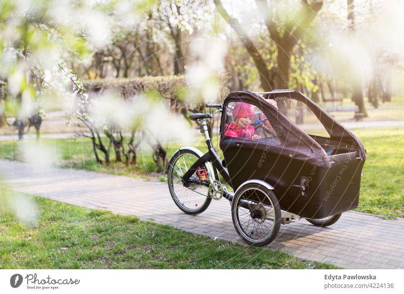 Kinder bei einer Fahrt mit einem Lastenfahrrad im Frühling Dreirad Lastenrad Tag Gesundheit Lifestyle aktiv im Freien Spaß Freude Park Fahrrad Zyklus Radfahren