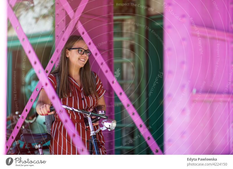 Glückliche junge Frau mit Fahrrad in der Stadt körperpositiv Übergewicht Übergrößenmodell urban Großstadt aktiv Menschen junger Erwachsener lässig attraktiv