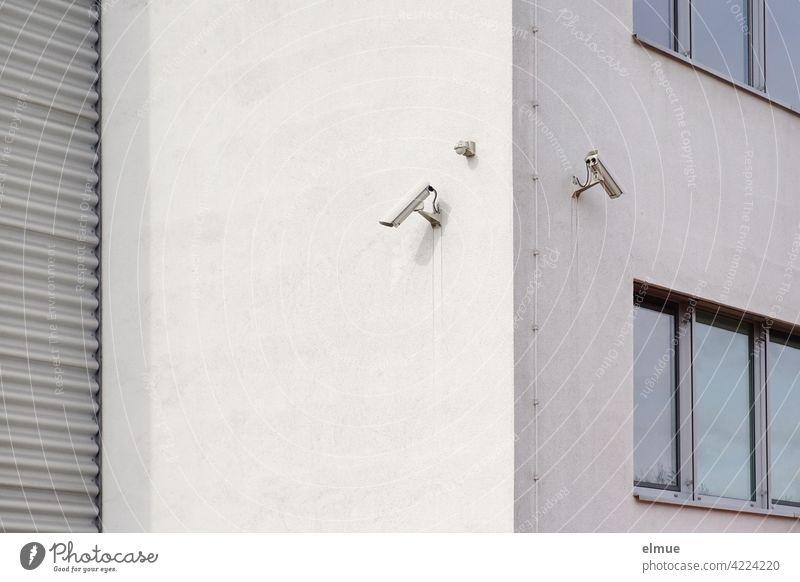 An einer Hausecke eines Zweckgebäudes mit Fenstern und Rolltor sind zwei Überwachungskameras angebracht / Sicherheitstechnik / Überwachung Sicherheitssystem