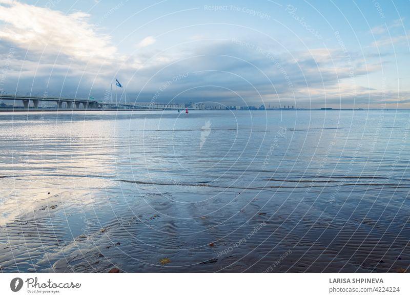 Schöne Sonnenaufgang am Strand von Park St. Petersburg ist 300 Jahre alt auf Golf von Finnland. Ruhige glatte Wasser mit Zirruswolken reflektiert, St. Petersburg, Russland.