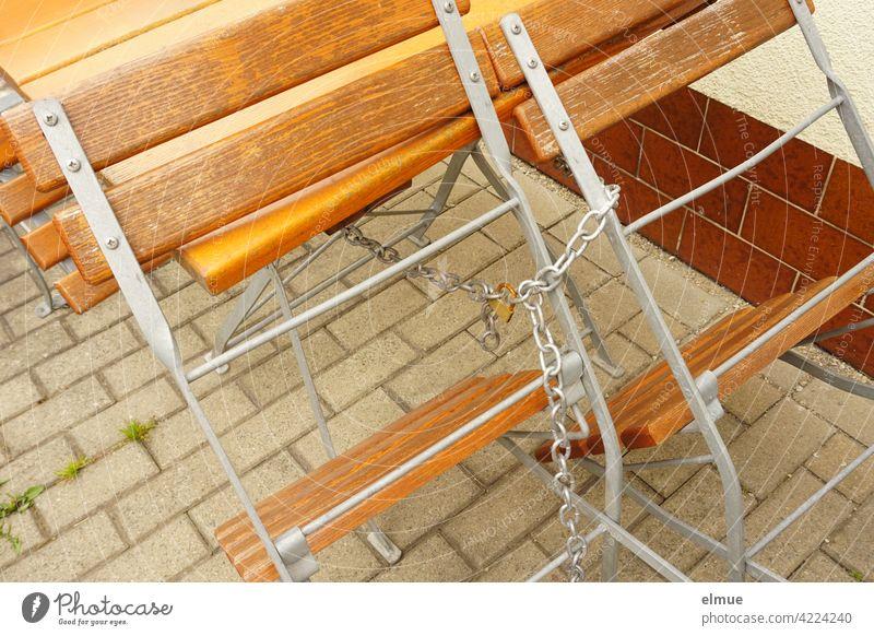 Holzstühle und Tisch im Biergarten sind mit einer Kette und einem Schloss versehen / geschlossen Holzstuhl Holztisch Stuhl Cafe Außenbereich Corona