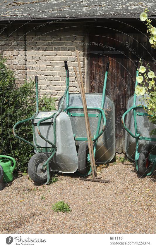 drei Schubkarren, eine Harke, ein Häcker und 2 Gießkannen haben Feierabend Gartengeräte Arbeitserleichterung Gartenschuppen Holztür Stockrose Kiesweg Metall