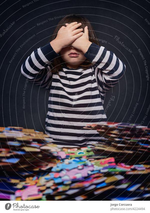 4 Jahre altes Mädchen blockiert mit einer Menge von Puzzleteilen, die ihre Augen mit ihren Händen bedecken. Puzzlestücke Geduldsspiel Stichsäge Spielzeug